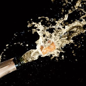 Celebration theme with splashing champagne, isolated on black background.